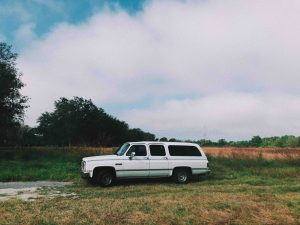 a white station wagon sits in a field