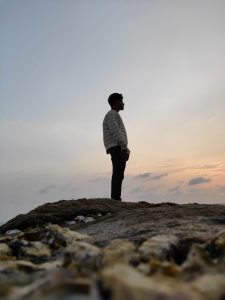 A person stands on some rocks in silhouette
