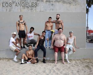 a group of 9 people of different races and sizes are grouped in front of a sign that reads 'Los Angeles'