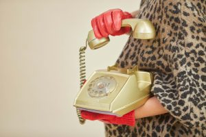 Person holding gold-coloured rotary telephone