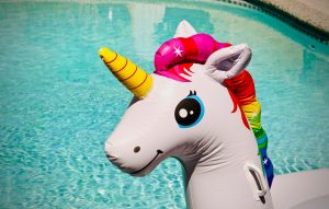 a blow up unicorn toy sits in a pool