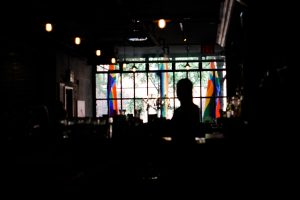 Photo shows the inside of a venue with rainbow flags displayed outside the windows
