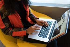 Long-haired person wearing a red and black jacket using MacBook Pro