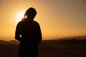 a person stands in the silhouette of sunset