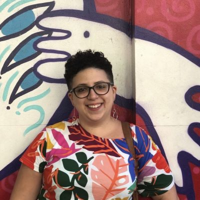 Image of Roz wearing a colourful patterned shirt in front of red, white, blue and black street art