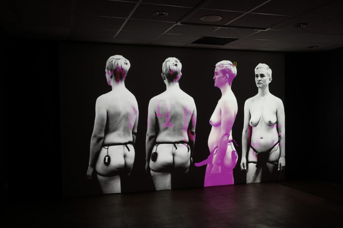 There are four images of the same person projecting on a wall in a large dark space. The person is shot at different angles, they are naked with short hair and wearing a harness around their waist.
