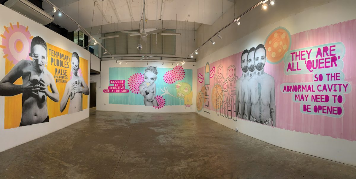 A photo of a large art gallery. The image shows three different artworks that are brightly coloured and pop-art style, with varying words about queer expression.