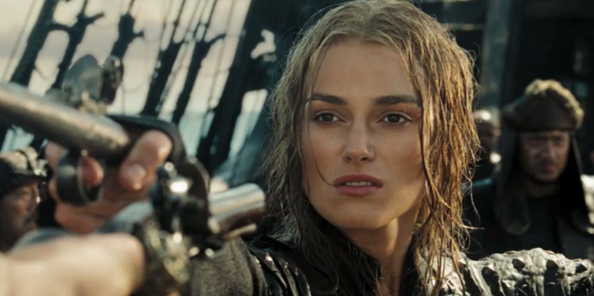 Keira Knightley, a white woman with brown hair, is seen in her role as Elizabeth Swan from Pirates of the Caribbean. She has short wet hair, is on a pirate ship and is holding a gun.