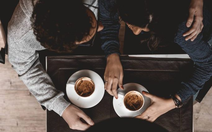 An overhead photo of two people drinking coffees.