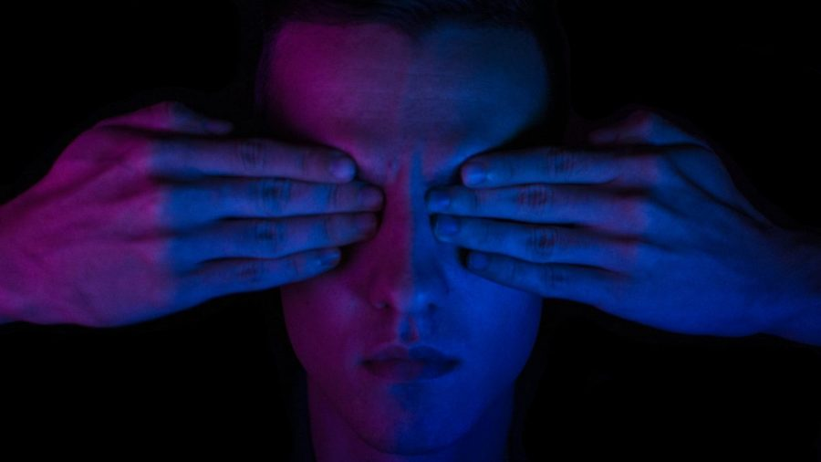A person's face is pictured with hands covering the eyes. The image is dark with pink and purple lighting.