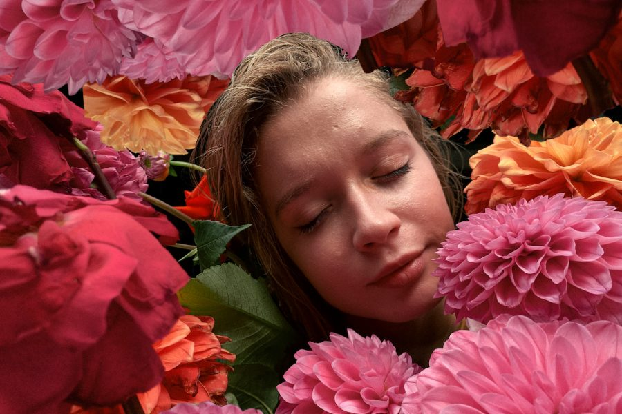 The face of person with blonde hair is seen in a colourful field of flowers. Their eyes are closed and the flowers are pink, orange and red and take up a majority of the frame.